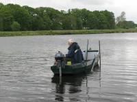 Dick heeft zijn boot geparkeerd en vist met de vaste hengel