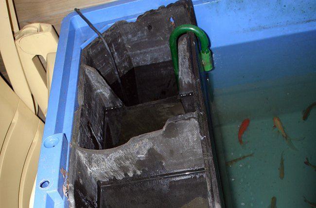 De zak met plastic voor de bacterie cultuur (linksboven); De spons-filters (rechts boven); de zak met korrels voor het filteren (links onder)